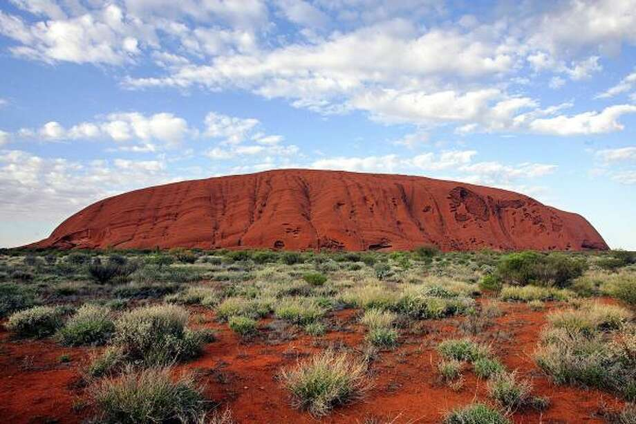 The large sandstone formation of Uluru (commonly known as Ayers Rock) rises 1,142 feet from the desert. This iconic monolith of Australia is one of the largest in the world, with a circumference of six miles. Photo: TORSTEN BLACKWOOD, AFP/Getty Images