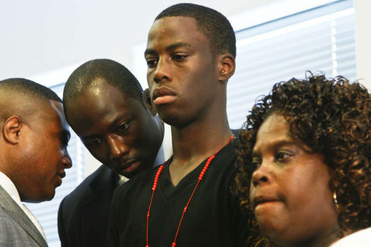 Chad Holley stands beside his mother, Joyce Holley as Quanell X, left, talks with lawyer Wilvin Carter during a press conference Tuesday in Houston.