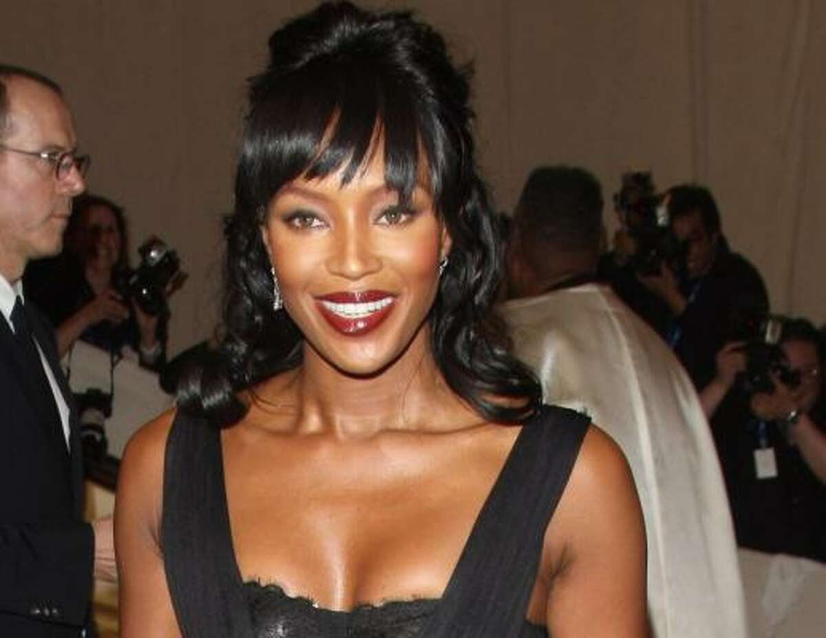 Naomi Campbell in Dolce & Gabbana looks stunning. Just watch out for flying cell phones.