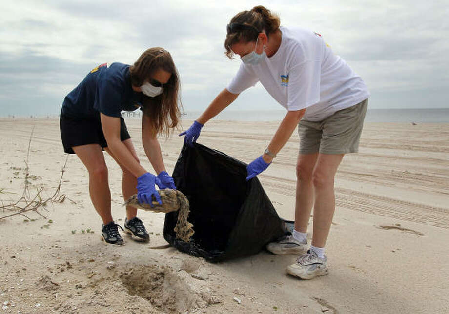 Megan Broadway, left, and Wendy Hatchett from the Institute for Marine Mammal Studies pick up a dead sea turtle Monday in Pass Christian, Miss. It is unknown if the turtle died because of the oil spill. Photo: Joe Raedle, Getty Images