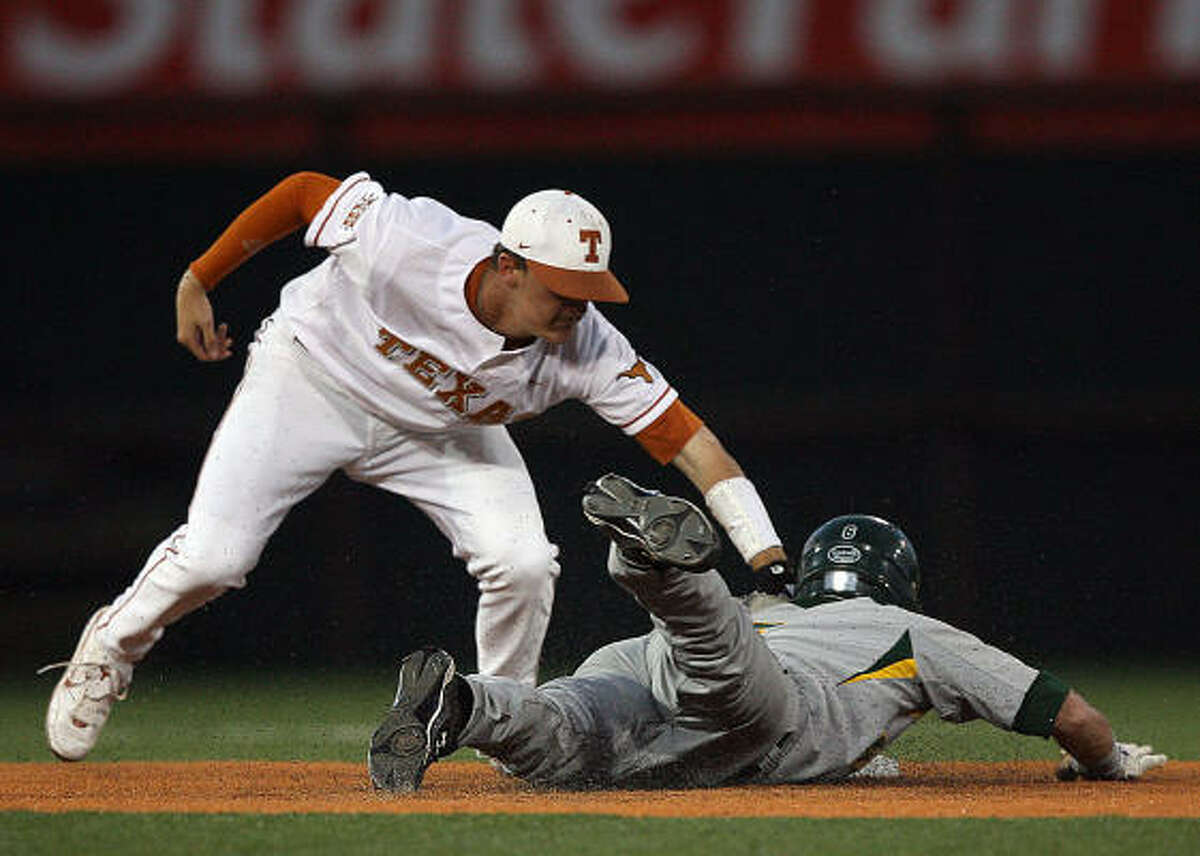 Texas shortstop Brandon Loy, left, tags out Baylor's Raynor Campbell on an attempted steal of second base in the first inning of Saturday's game in Austin. Texas won 2-1 in 14 innings.