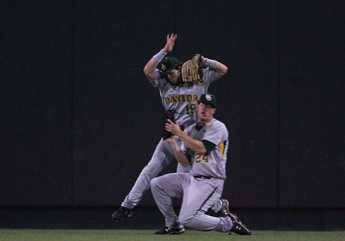 Baylor left fielder Logan Vick, rear, nearly collides with center fielder Don Lambert after they run down a fly ball hit by Texas' Tant Shepherd during the third inning.