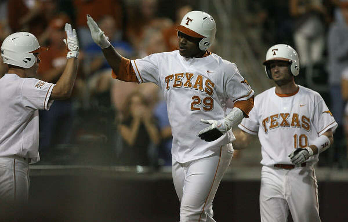 Texas' Kevin Keyes, center, gets a high-five from Jordan Etier after scoring on a double by Kevin Lusson in the second inning.