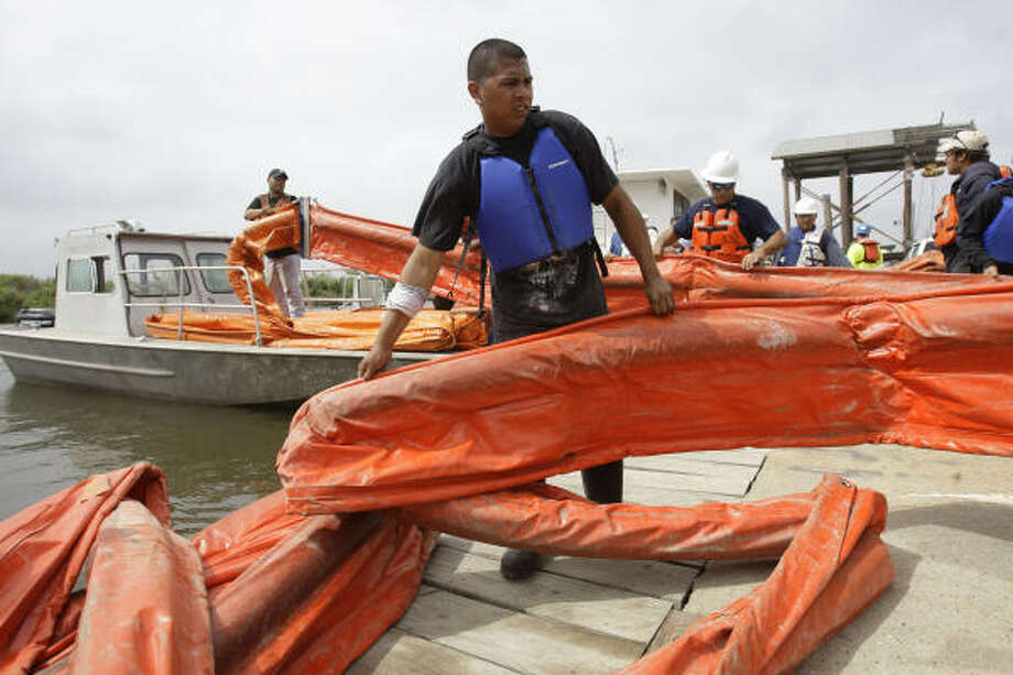Wastewater Specialities employee Lenin Castro of New Orleans helps load 6,000 feet of containment boom onto boats in Shell Beach. The boom will be used to protect the fragile Louisiana marshes from the Deepwater Horizon oil spill. Photo: Melissa Phillip, Chronicle