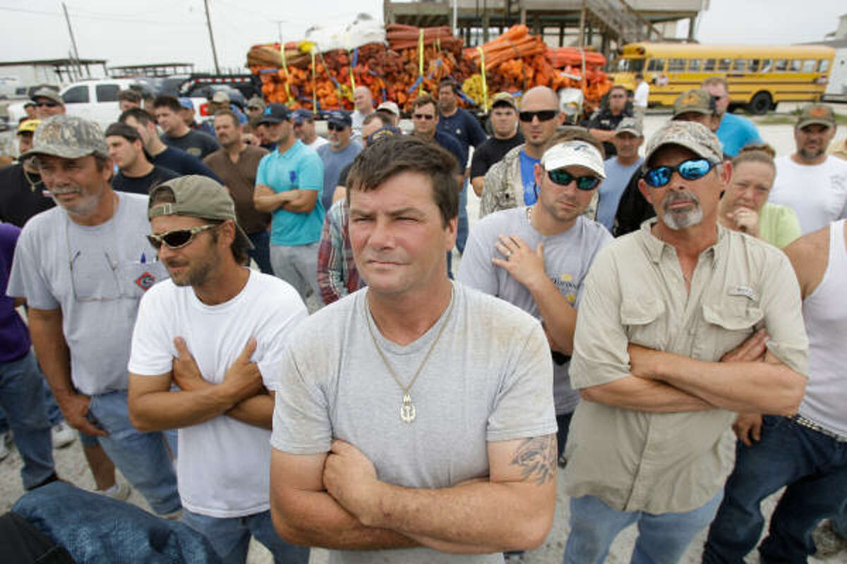 Fishermen Jermone Ronquille, center, David Palmer, left, and Glenn Sanchez, right, listen to instructions for the Vessel of Opportunity program in which fishermen will be paid to use their boats to help with the oil spill from the Deepwater Horizon. Most would be deploying containment boom. High wind and rough water cause the a delay until tomorrow.