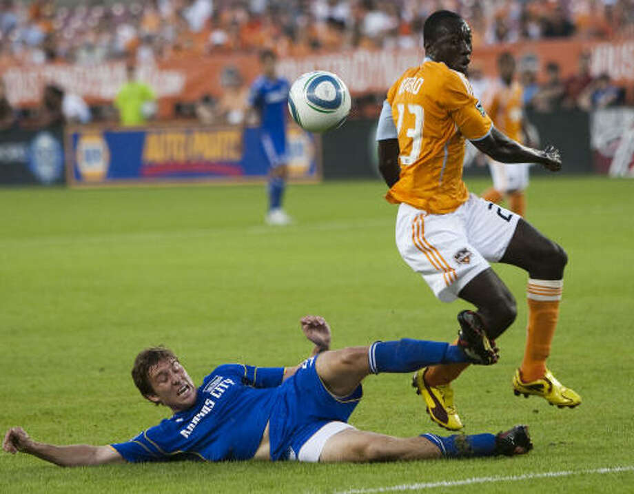 Dynamo forward Dominic Oduro leaps past Kansas City Wizards defender Matt Besler in the first half of Saturday's game at Robertson Stadium. The Dynamo won 3-0. Photo: Brett Coomer, Chronicle