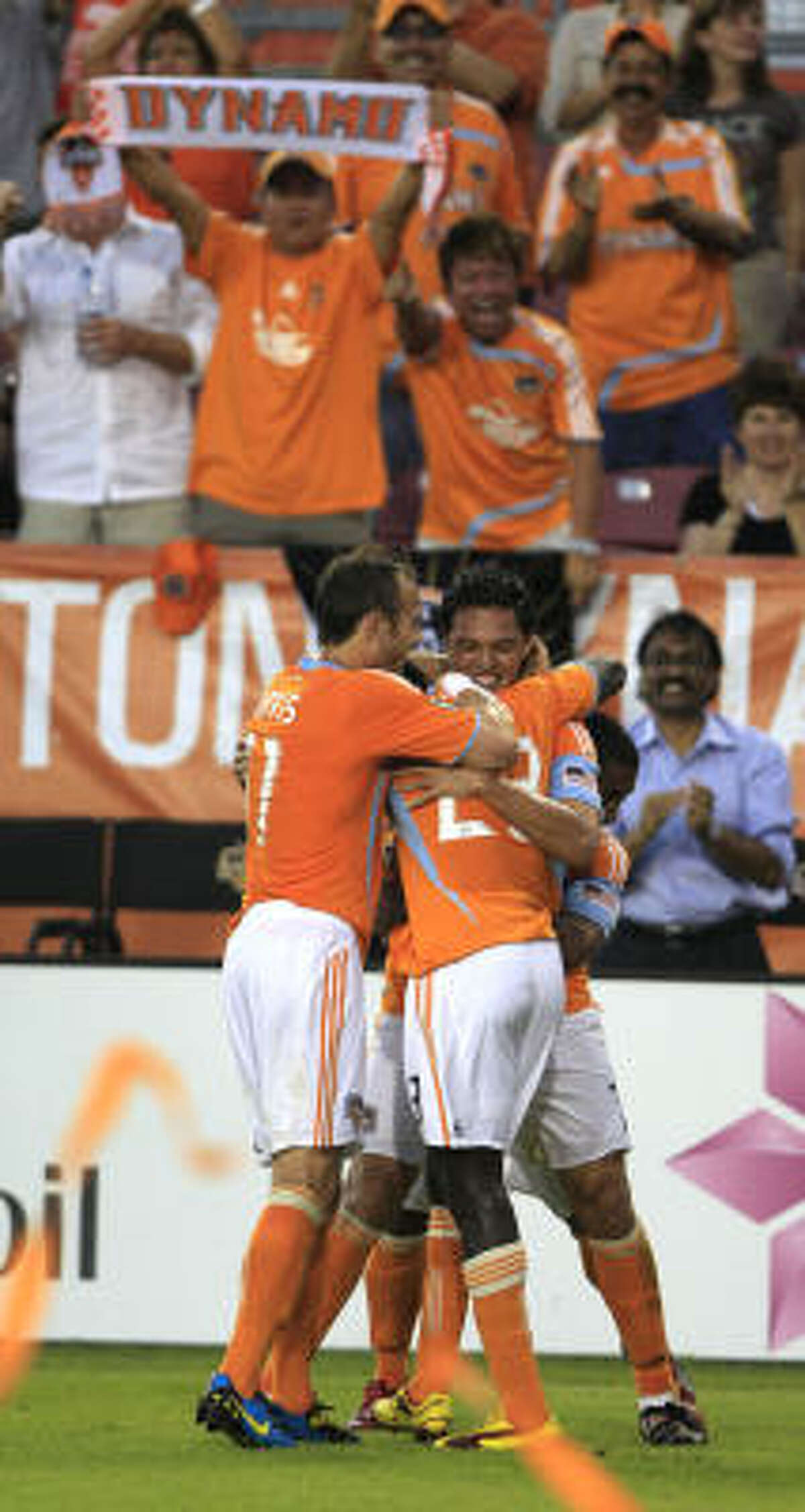 Dynamo forward Luis Landin is hugged by teammates Brad Davis (11) and Dominic Oduro after scoring a goal in the first half.