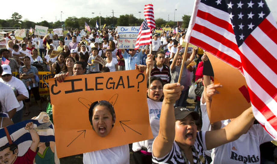 "Houston: A protester displays the Spanish word for ""illegal"" at Burnett Bayland Park. Photo: Brett Coomer, Chronicle"