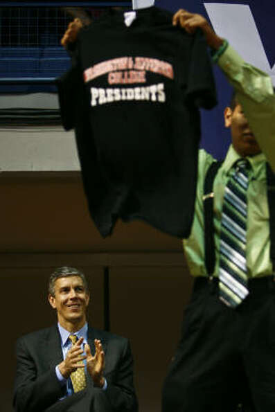 U.S. Education Secretary Arne Duncan applauds as Steven Perez holds up a shirt from Washington & Jef