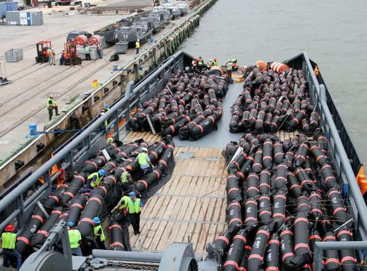 Workers secures inflatable oil containment booms on the deck of an offshore service vessel at the Mississippi State Port in Gulfport, Miss., on Friday April 30, 2010. The equipment is will be deployed along the west end of Ship Island, south of Gulfport.