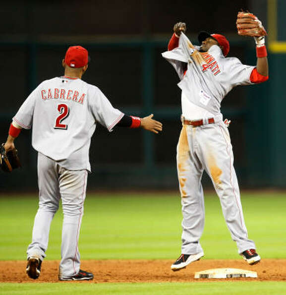 Reds second baseman Brandon Phillips, right, throws off his jersey after he turned a game-ending dou