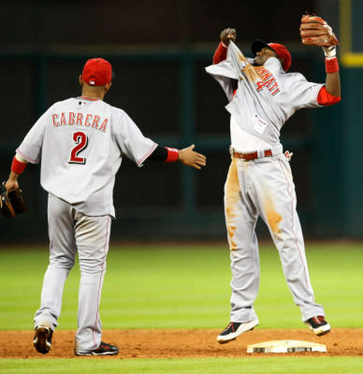 Reds second baseman Brandon Phillips, right, throws off his jersey after he turned a game-ending double play on a hit ball by Astros third baseman Geoff Blum as the Reds sweep the Astros during a 4-2 victory.