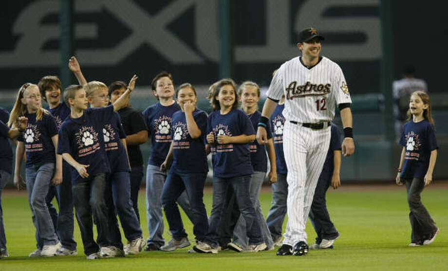 Astros shortstop Tommy Manzella smiles as he walks with students from Kaufman Elementary School, who sang the National Anthem, prior to the start of the Thursday's game. Photo: Julio Cortez, Chronicle
