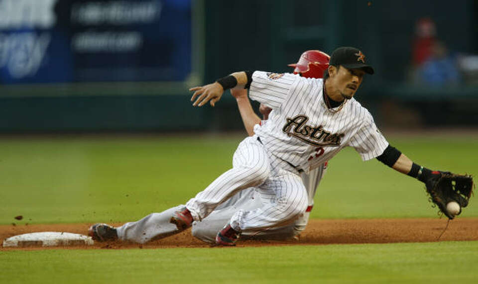 Astros second baseman Kazuo Matsui, front, makes a stop on a thrown ball by Astros catcher Humberto