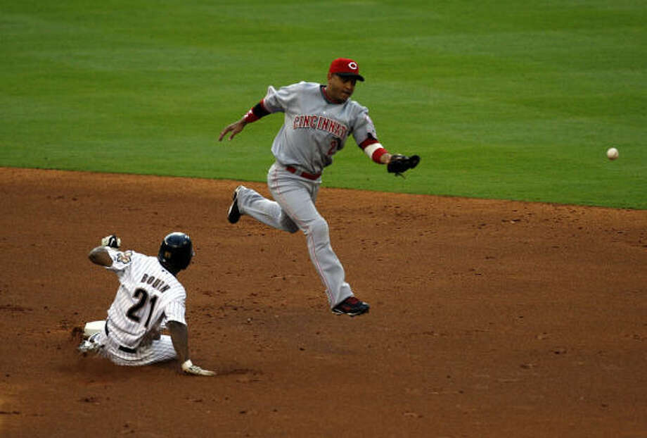 Michael Bourn slides safely into second base past the bobbled ball of Cincinnati's Orlando Cabrera. Photo: Johnny Hanson, Chronicle