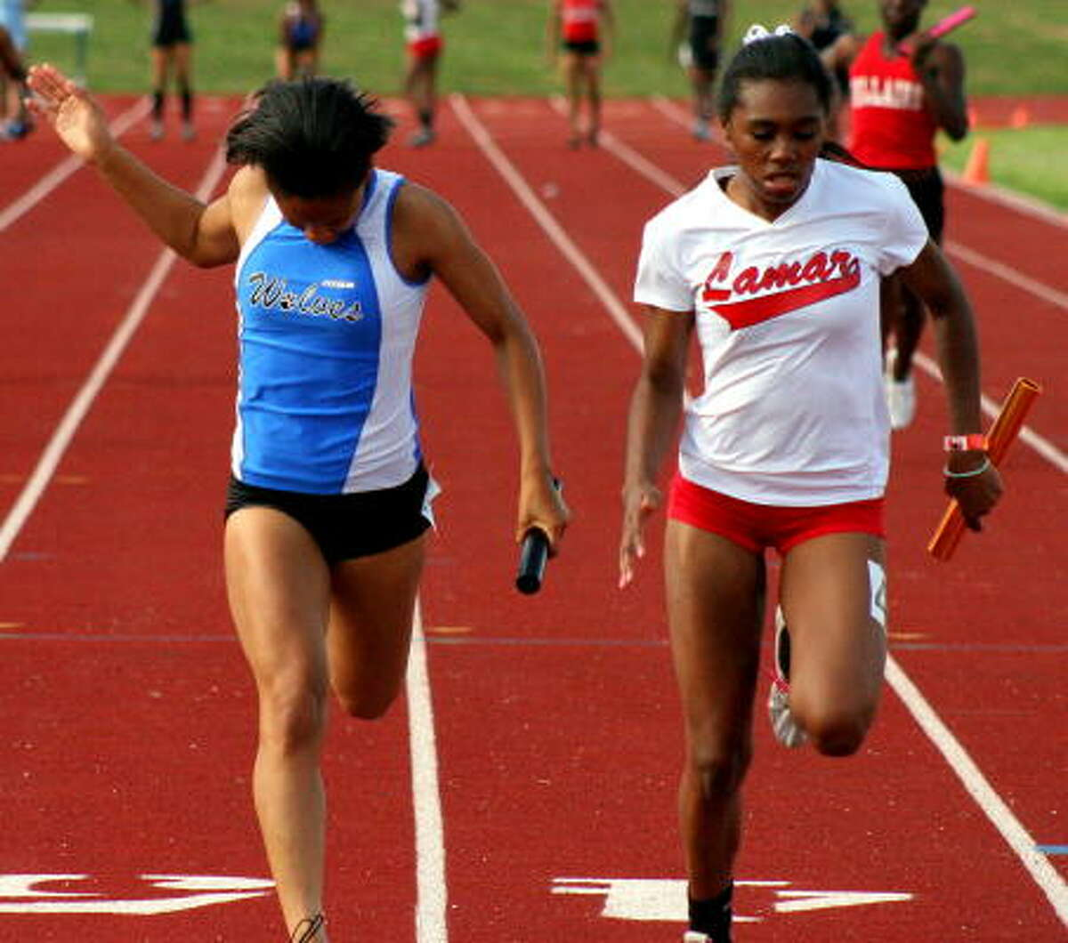 Lamar's Ayanne Magee, right, edges out Westside's Kirby Miller at the tape to take a 400-meter relay victory.