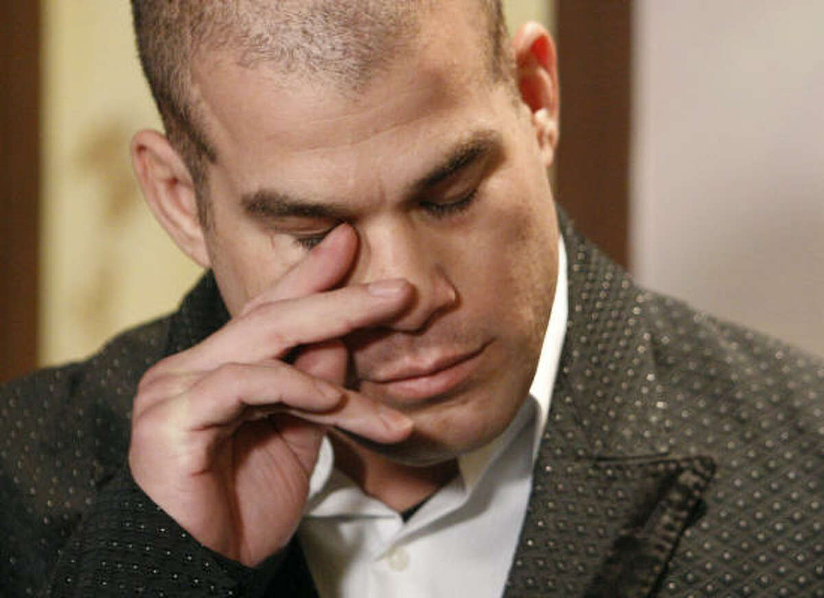 Former Ultimate Fighting champion Tito Ortiz wipes a tear from his eye as he listens to his attorney speak to the media Monday. Ortiz claims his ex-adult film star girlfriend, Jenna Jameson, is addicted to Oxycontin, and he blames her drug use for his arrest Monday on suspicion of domestic violence.