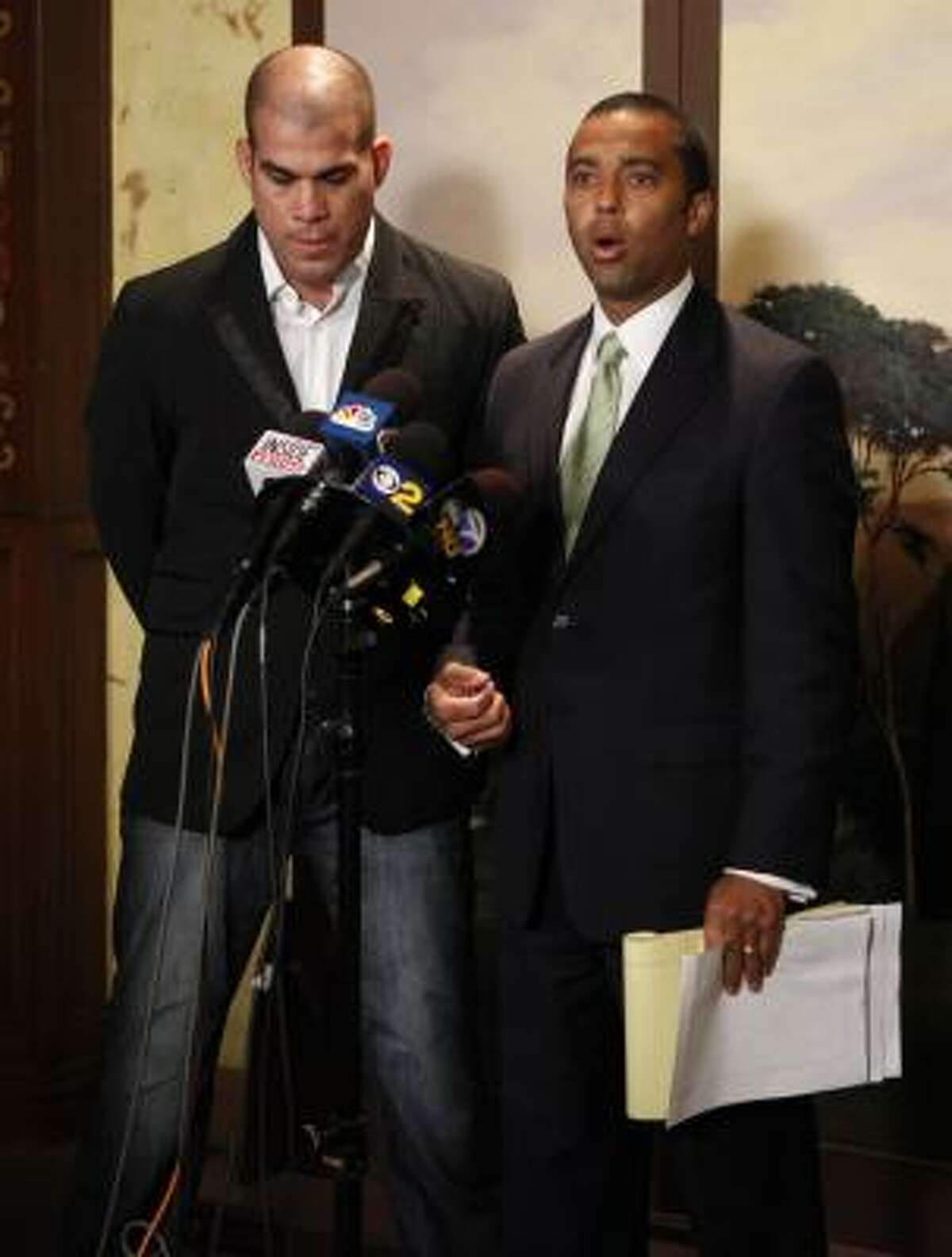 Former Ultimate Fighting champion Tito Ortiz, left, listens as his attorney Chip Matthews, right speaks to the media Monday, April 26, 2010, after Ortiz was released from jail. Matthews said the Ortiz found drugs in his home Monday morning, leading to the confrontation that ended with Ortiz's arrest.