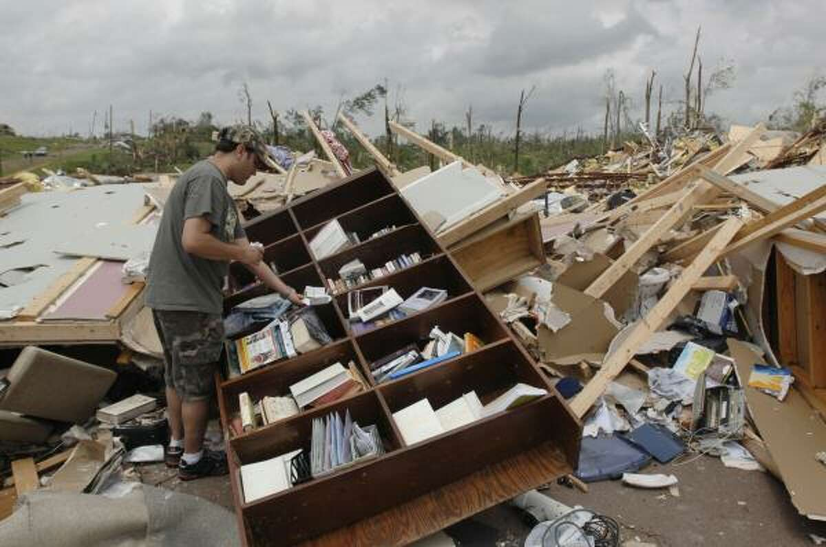 Jason Newell tries to salvage what he can from a destroyed church in Yazoo City, Miss.