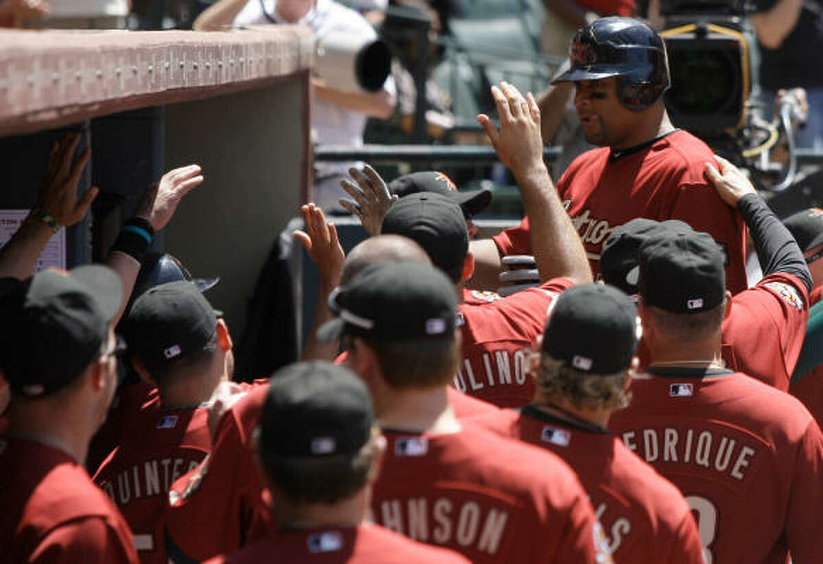 Carlos Lee receives congratulations after scoring on a triple and one-base error.
