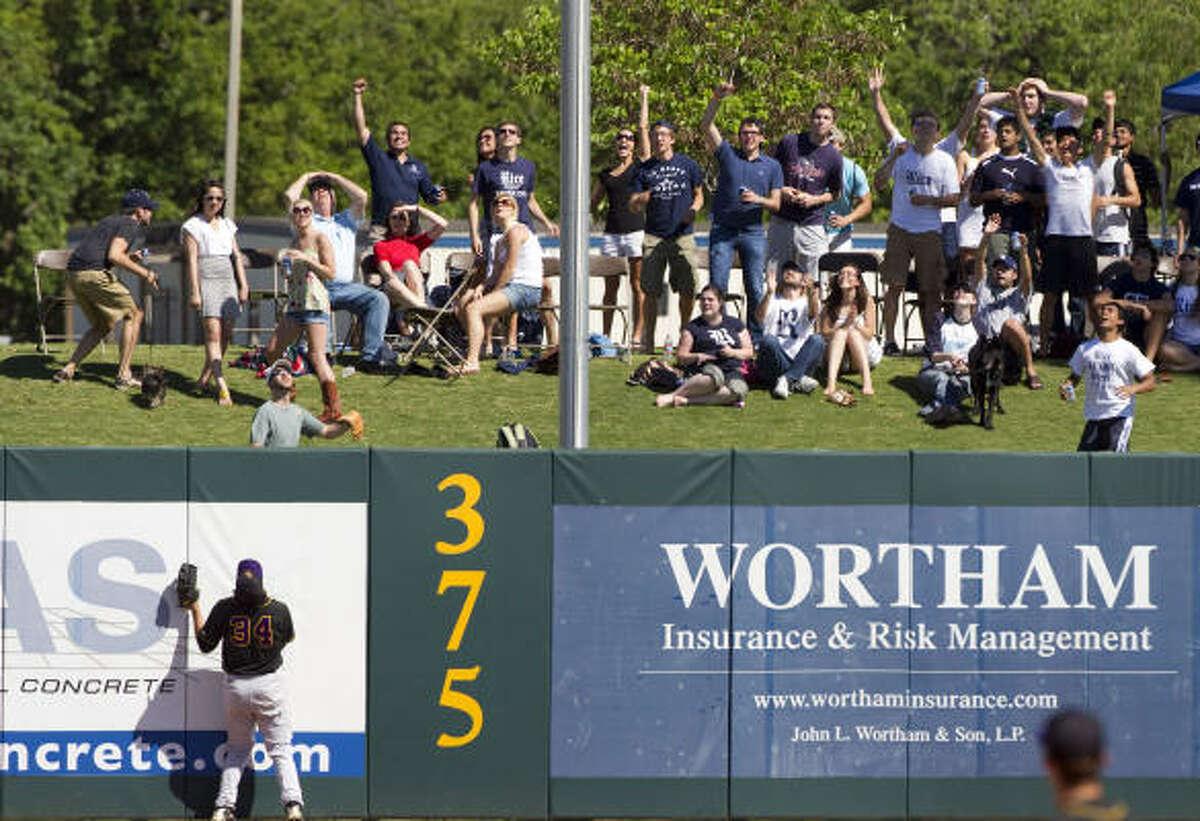 East Carolina left fielder Devin Harris looks up as Rice fans celebrate Anthony Rendon's three-run homer.
