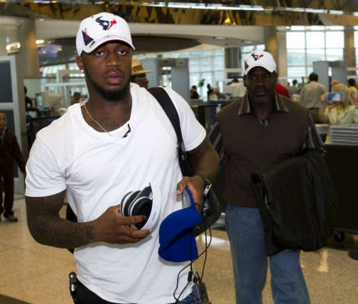 Texans first round draft pick Kareem Jackson walks with his father, Hezekiah, after arriving at Hobby Airport on Friday.