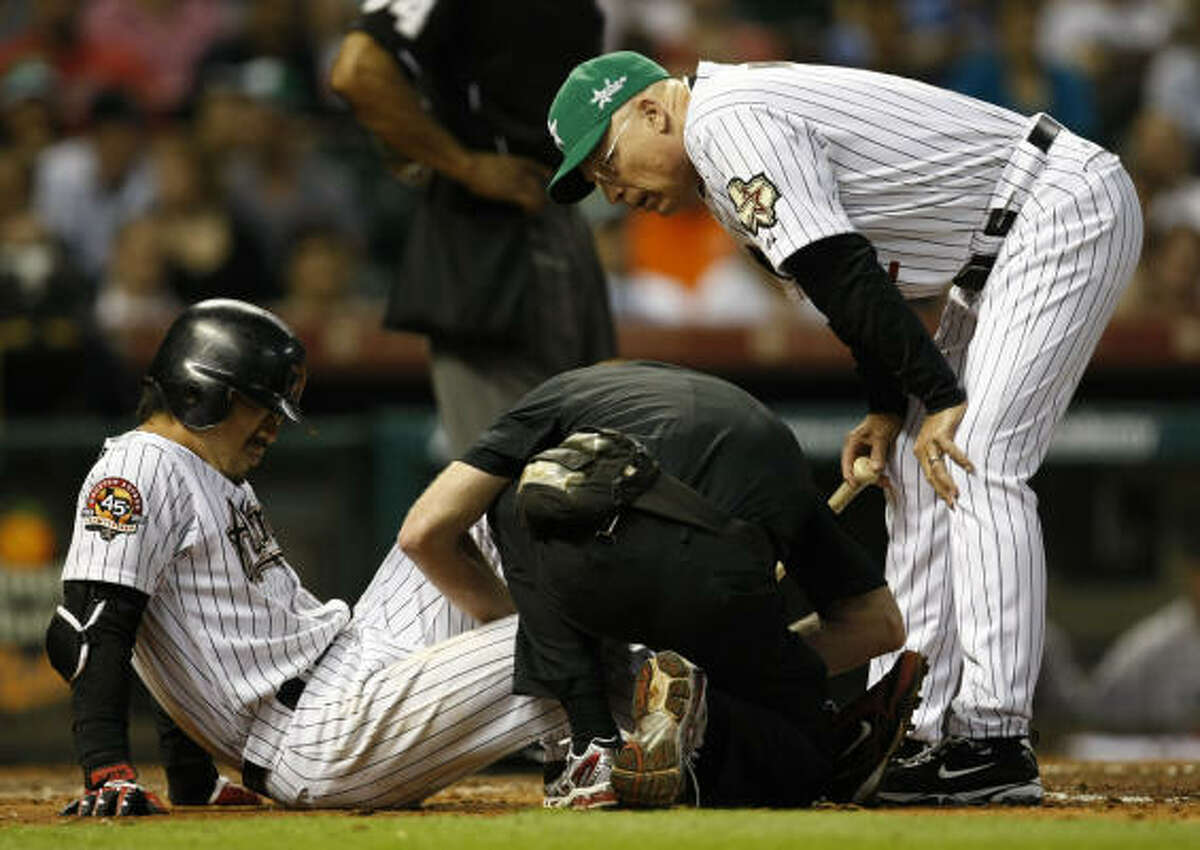 Astros second baseman Kazuo Matsui, left, receives medical treatment after fouling a ball off his leg.