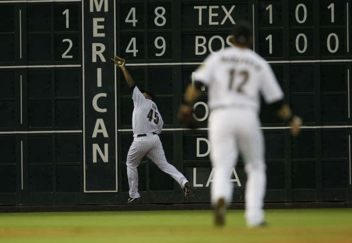 Astros left fielder Carlos Lee makes a running catch near the wall on a fly ball by Marlins first baseman Jorge Cantu.