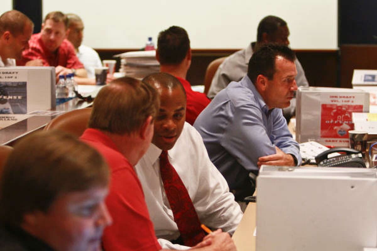 Texans coach Gary Kubiak (fourth from left) sits in the draft room Thursday night.