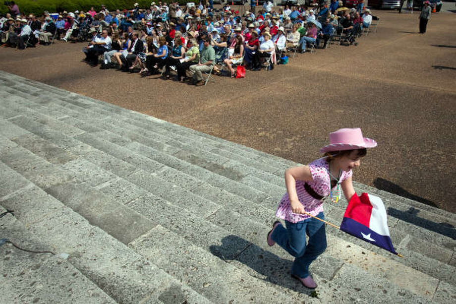 Rowan Marshall, 5, carries a Texas flag as she runs up the steps of the the San Jacinto Monument during ceremonies commemorating the 174th Anniversary of the Battle of San Jacinto. Rowan attended the event with her father Greg Marshall and sister Brenna.  She is a descendant of John Henry Dillard, who fought and died at the Alamo, and has attended the ceremony every year since she was born. Photo: Smiley N. Pool, Chronicle