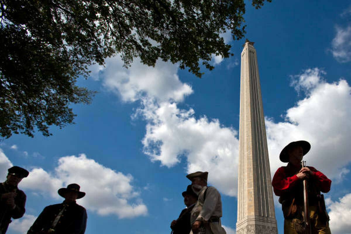 Members of the Texas Army, including Carl Hill, right, find the shade of a tree as they prepare for ceremonies commemorating the 174th Anniversary of the Battle of San Jacinto at the San Jacinto Monument in La Porte. The group is the state's Official 1836 Ceremonial and Reenactment Group.