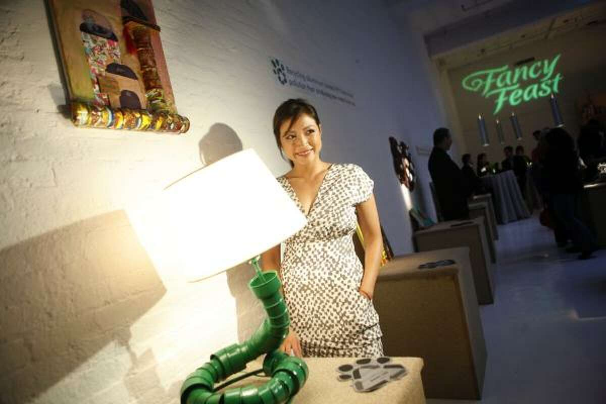 Eco-friendly designer Kahi Lee poses with her lamp made from used aluminium cat food cans.
