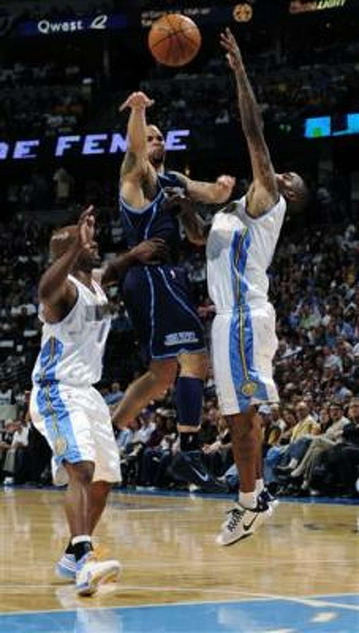 Deron Williams, del Jazz, pasa entre Chauncey Billups (izquierda) y J.R. Smith, de Denver, para anotar dos de sus 33 puntos en el Juego 2 de la primera ronda de playoffs en la Conferencia del Oeste que ganó Utah 114-111 a los Nuggets y empatar 1-1 la serie, el lunes 19 de abril de 2010, en Denver, Colorado.