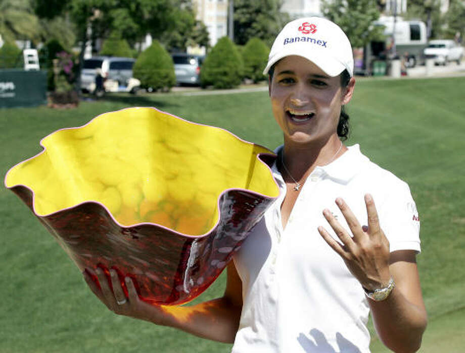 Lorena Ochoa holds up the Kelly Jo Dowd trophy along with four fingers to signify her four straight LPGA wins in April 2008. Photo: Reinhold Matay, AP