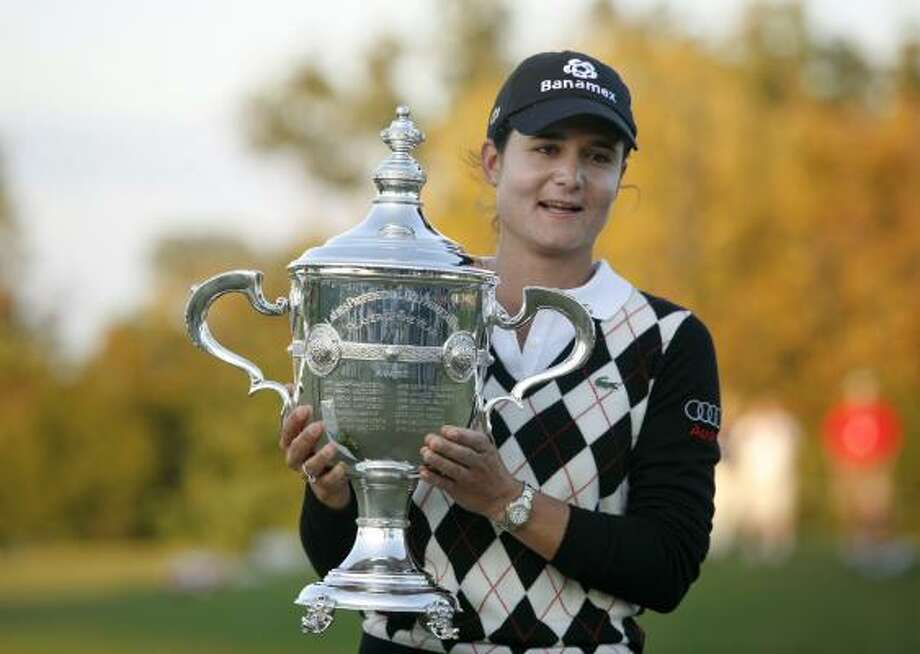 Ochoa holds her LPGA player of the year trophy on the 18th green after the final round of the LPGA Tour Championship on Nov. 23, 2009, in Richmond, Texas. Ochoa finished second in the tournament to Anna Nordqvist, but won her fourth consecutive player of the year award. Photo: Eric Kayne, AP