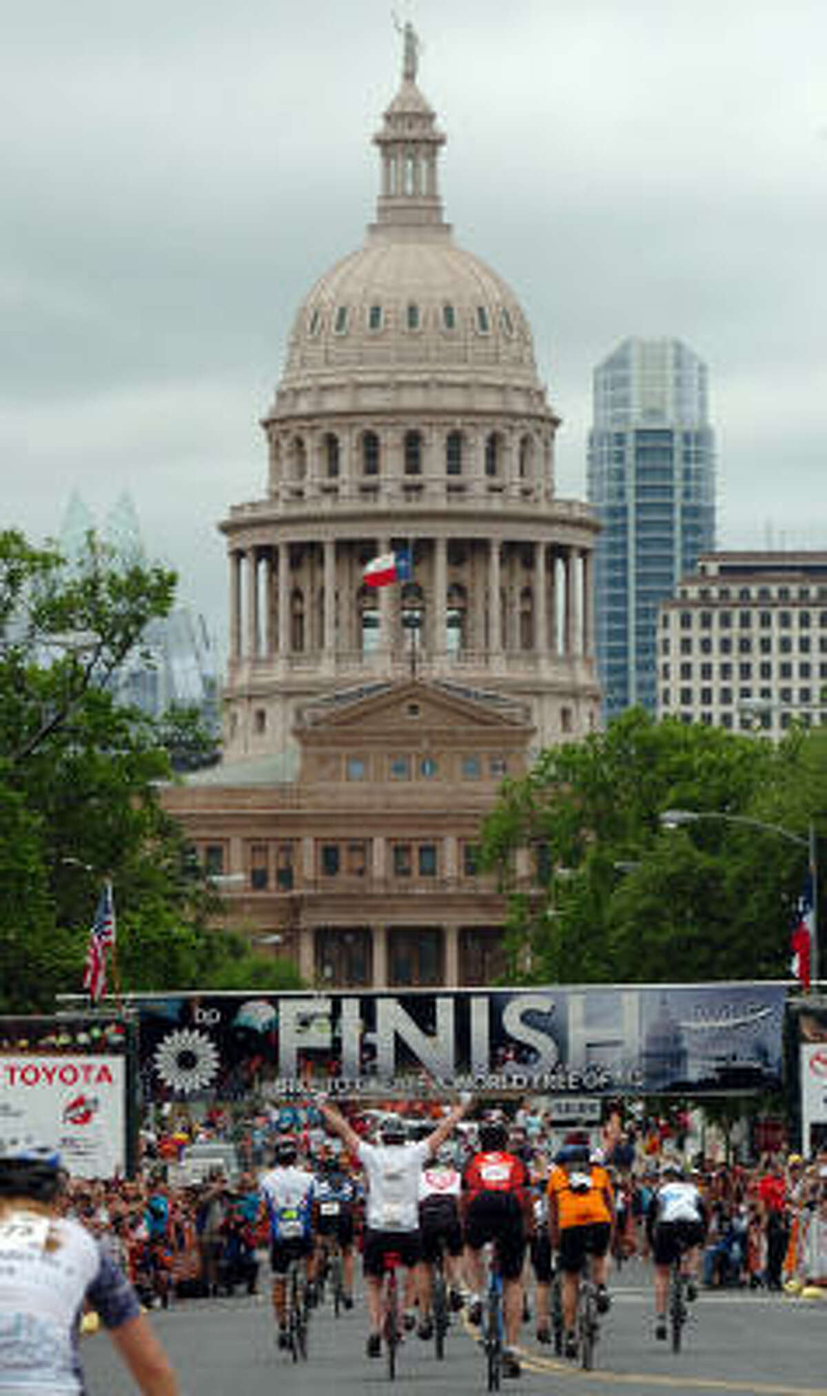 MS 150 riders celebrate as they cross the finish line Sunday morning near the Texas State Capitol.