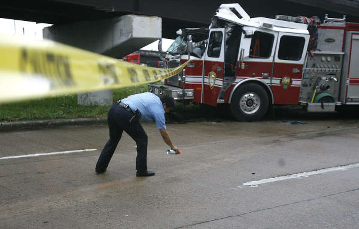 Houston Police Officer Rolando Saenz, Crash and Reconstruction Unit, sprays the skid marks as he investigates the cause of the Houston Fire Station 13 pumper truck accident on the service road for Highway 290 near Magnum where three firefighters were injured and transported to the hospital with non life threatening injuries.