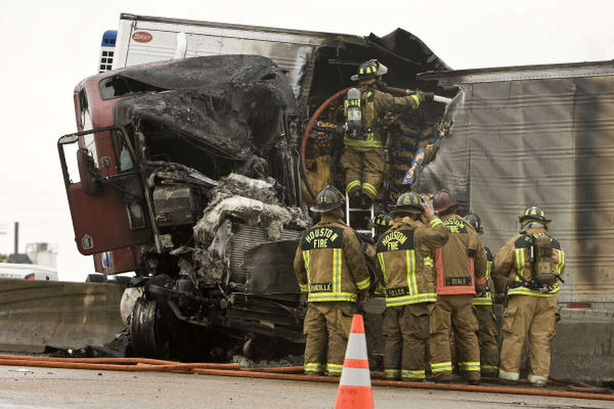 Emergency personnel work at the scene of an accident involving a tractor trailer rig carring produce which caught fire on Interstate 10 eastbound near Taylor in Houston.