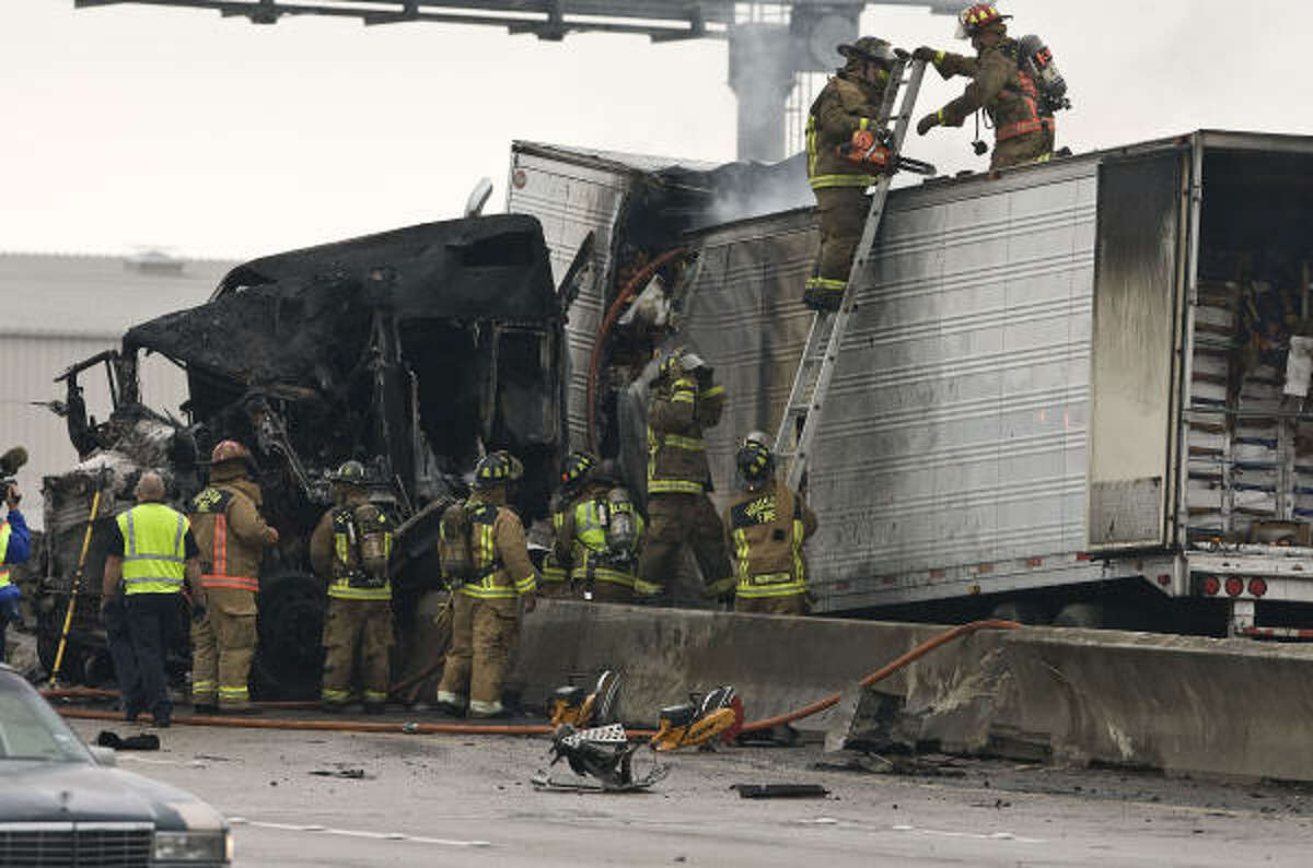 Emergency personnel work at the scene of an accident involving a tractor trailer rig carring produce which caught fire on Interstate 10 eastbound near Taylor street.