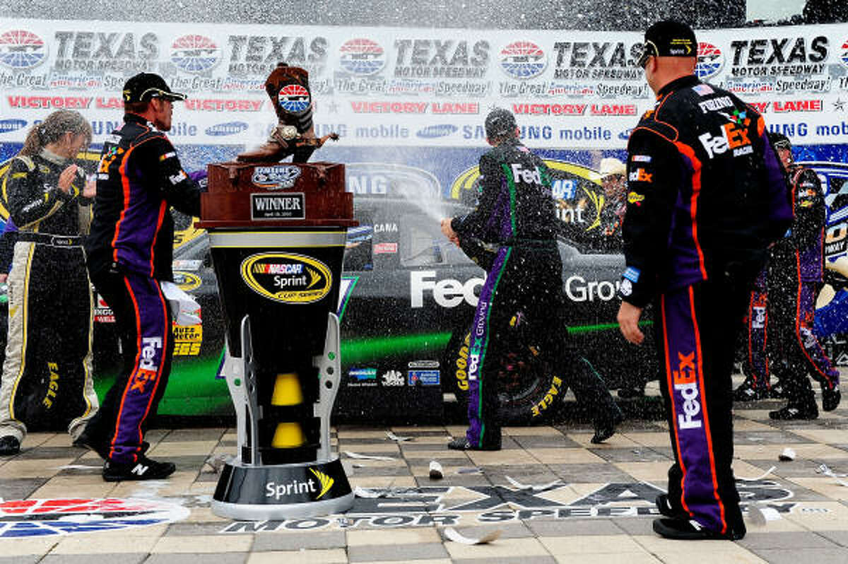 Denny Hamlin, driver of the No. 11 FedEx Ground Toyota, celebrates with crew members in Victory Lane.