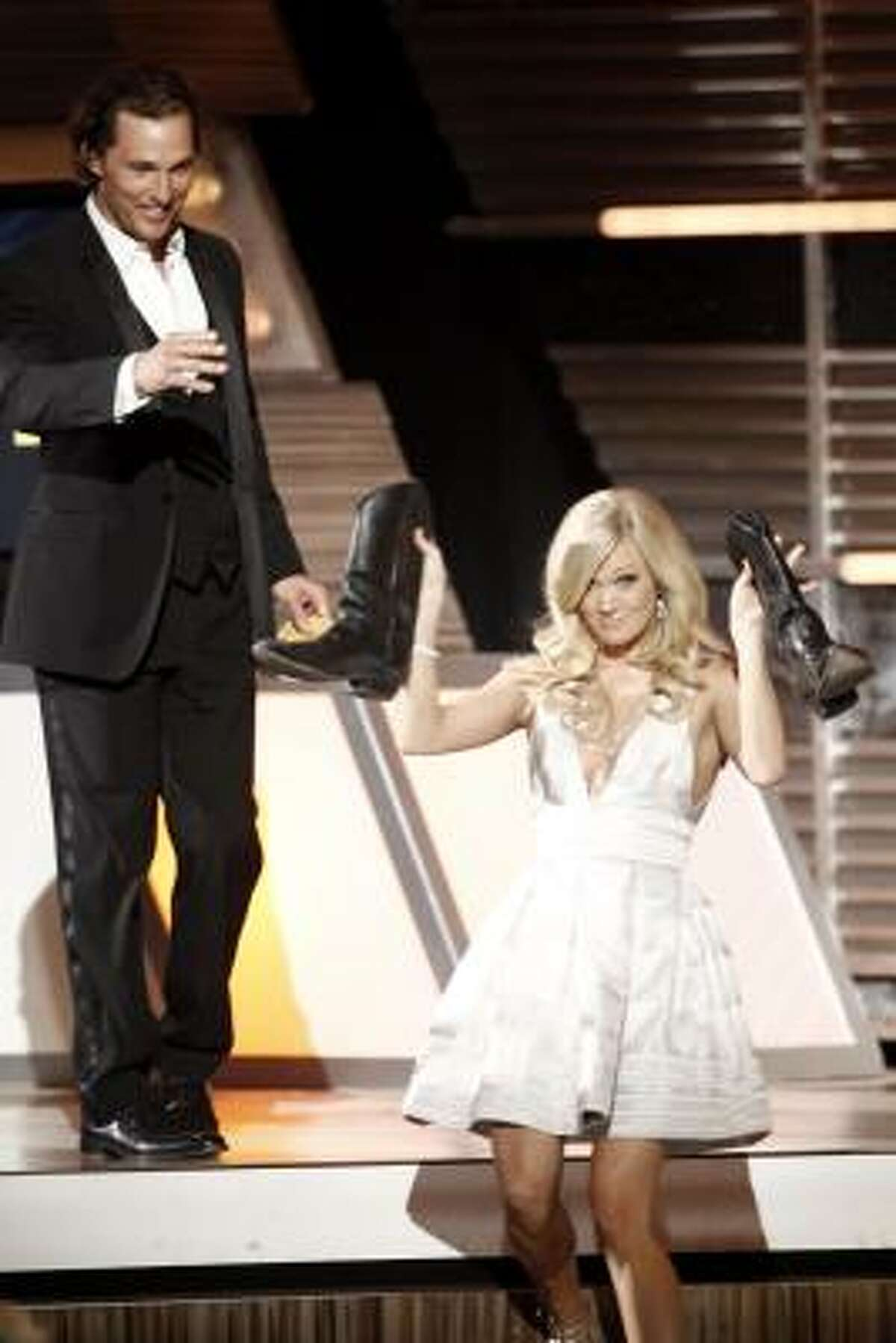 Matthew McConaughey, left, gives Carrie Underwood a pair of boots at the 45th Annual Academy of Country Music Awards.