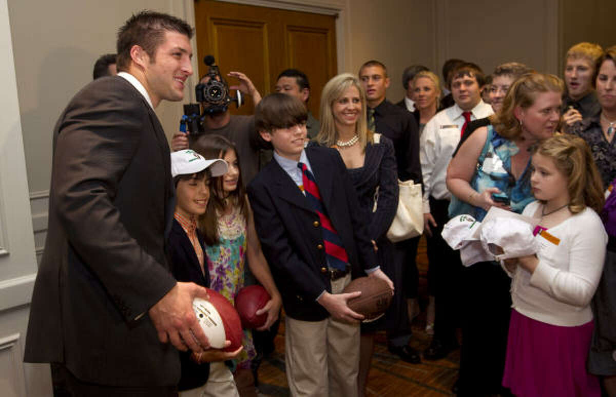 "Heisman Trophy winner and two-time national champion at Florida Tim Tebow poses for photos and signs autographs before speaking at the Source for Women's ""Game for Life"" banquet at the Westin Galleria."