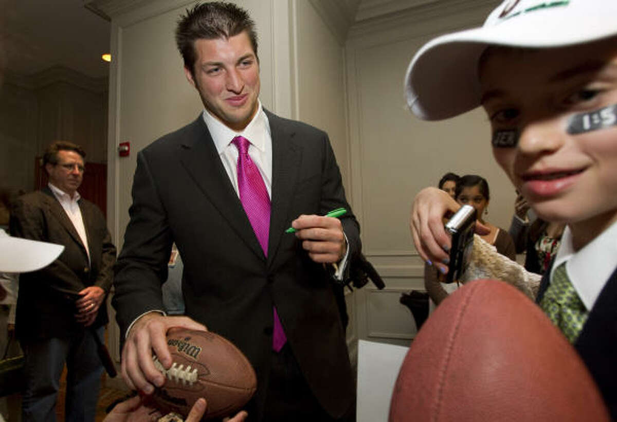 Heisman Trophy winner and former Florida quarterback Tim Tebow happily signed what seemed like an endless amount of autographs, grinning for every photo and wrapping his arms around everyone.