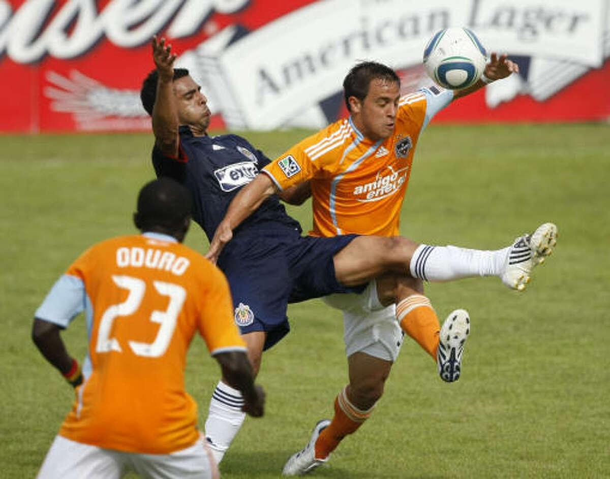 Dynamo forward Danny Cruz, right, and Chivas USA defender Michael Umana battle for the ball.
