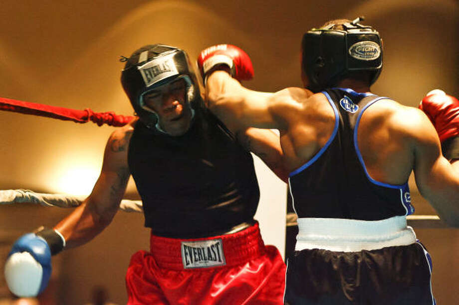 """Jaquis Davis, left, tries to avoid a punch from Anthony Domino during their 180-pound bout Friday at the """"Rumble Returns to Humble II"""" event at the Humble Civic Center. Davis won the match. Photo: Michael Paulsen, Chronicle"""