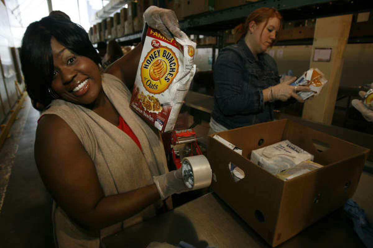 Former American Idol finalist LaKisha Jones (season 6) hams it up for the camera as she works along with other volunteers for the first time in the Feeding America's local food bank in Houston.