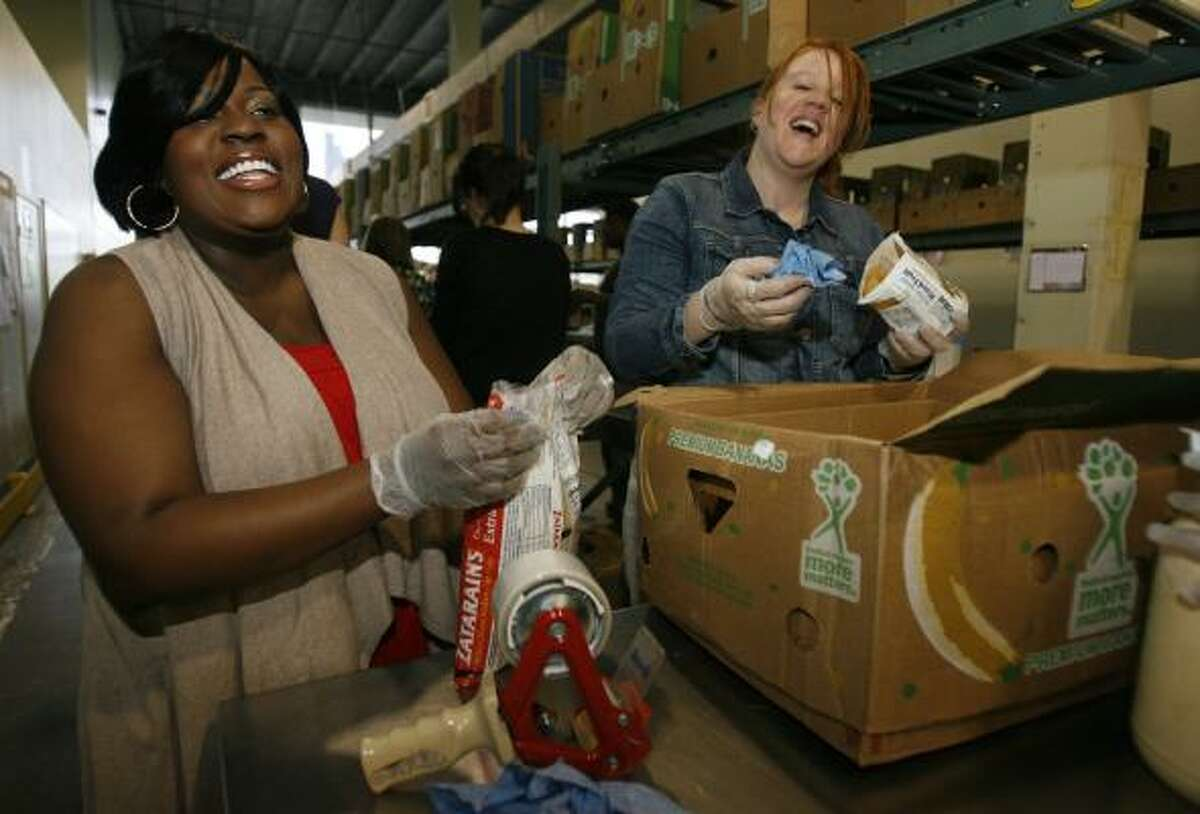 Former American Idol finalist LaKisha Jones (season 6) and Houston Food Bank Grant Manager Stacy Laster laugh as they work the food line in the Feeding America's local food bank in Houston, one of the beneficiaries of