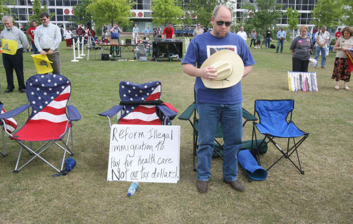 Darrell Goodwin bows his head in prayer before a tea party rally at Discovery Green Park in Houston.