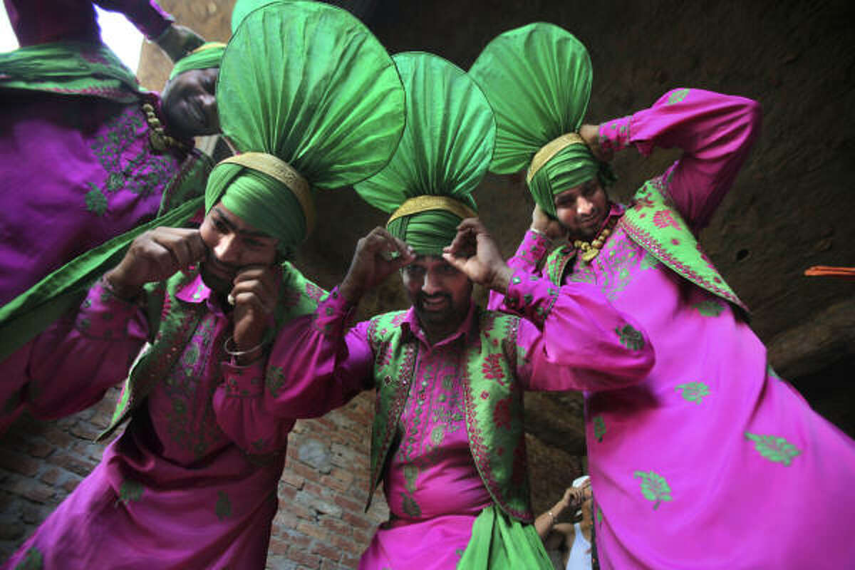 Folk artists in their traditional attire make final adjustments looking into a mirror placed on the floor, before performing traditional folk dance of Bhangra in a wheat field, as part of Baisakhi celebrations in Ajnala, some 35 kilometers (22 miles) from Amritsar, India, Monday, April 12, 2010. Baisakhi, a harvest festival celebrated in the Punjab region also marks the beginning of the Sikh New Year.
