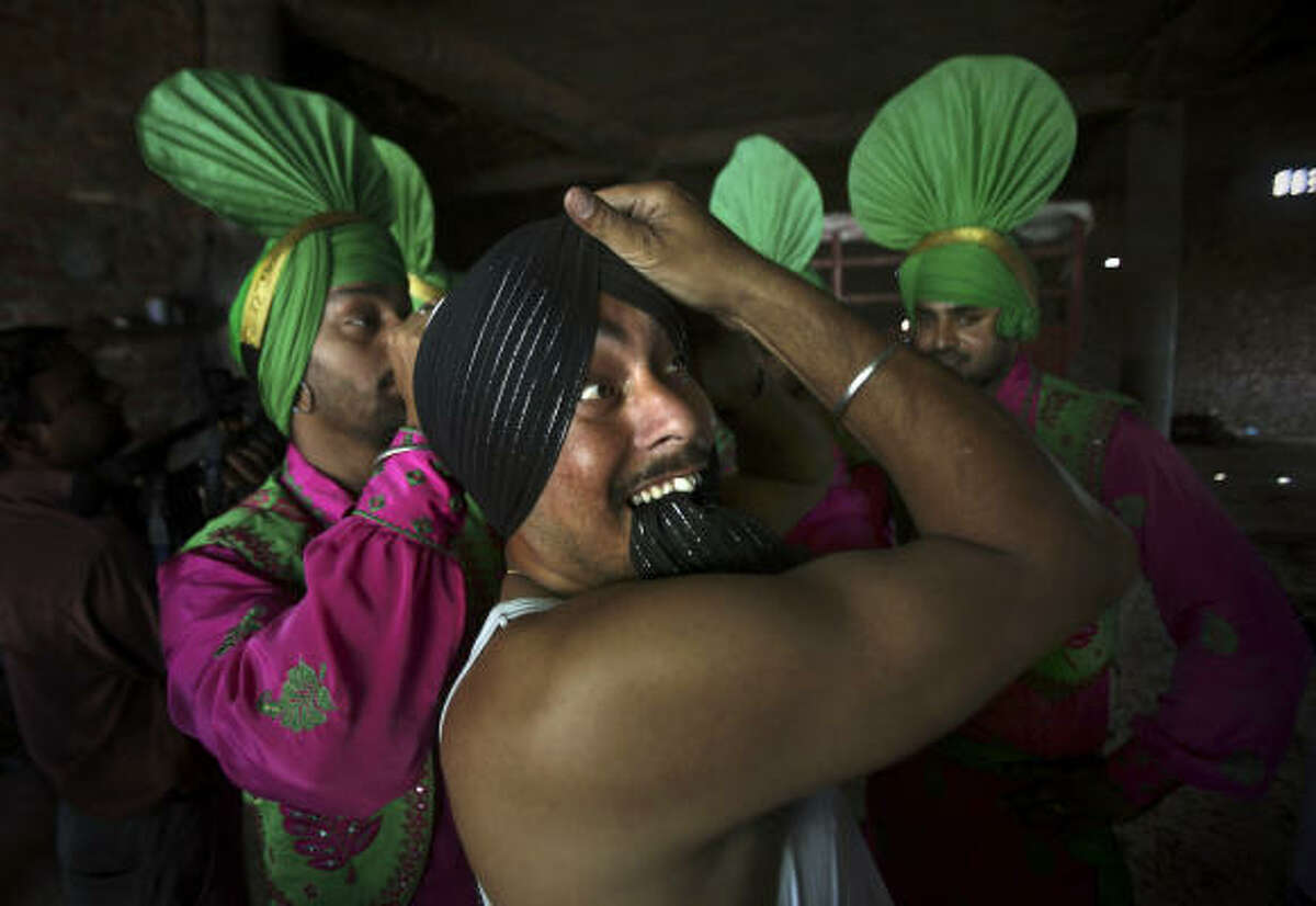 A folk artist adjusts the turban of his colleague before performing traditional folk dance of Bhangra in a wheat field, as part of Baisakhi celebrations in Ajnala, some 35 kilometers (22 miles) from Amritsar, India, Monday, April 12, 2010. Baisakhi, a harvest festival celebrated in the Punjab region, also marks the beginning of the Sikh New Year.